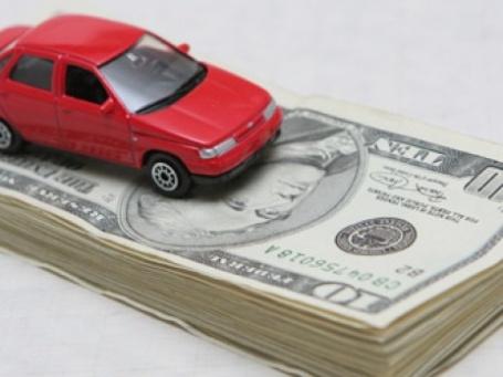 Макет автомобиля ВАЗ и долларовые купюры. Фото: ИТАР-ТАСС