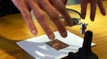 Филателист рассматривает марки под лупой. Фото: AFP