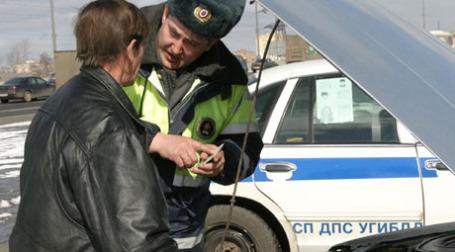 Инспектор ГИБДД и хозяин автомобиля во время прохождения ТО. Фото: PhotoXPress