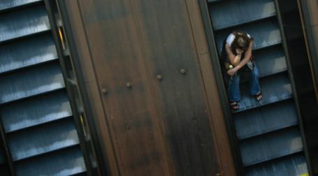 Девушка сидит на эскалаторе, едущем вниз. Фото: Brian Jeffery Beggerly/flickr.com