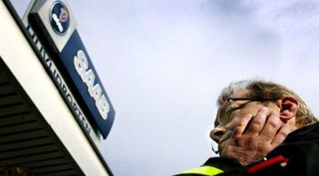Мужчина у вывески Saab. Фото: AFP