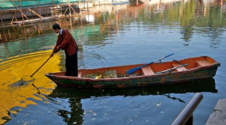 Китайский старик вылавливает мусор из воды. Фото: yewenyi/flickr.com