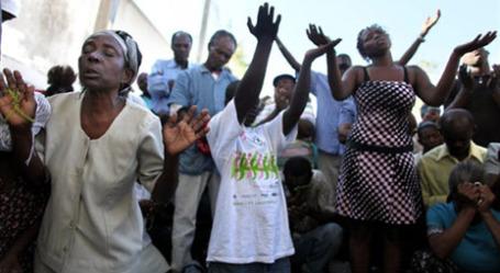 Гаитяне молятся рядом с разрушенным кафедральным собором в городе Порт-о-Пренс. Фото: AFP