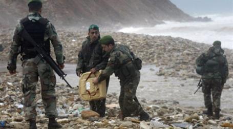 Военные в поисках погибших на берегу, недалеко от места катастрофы. Фото: AFP