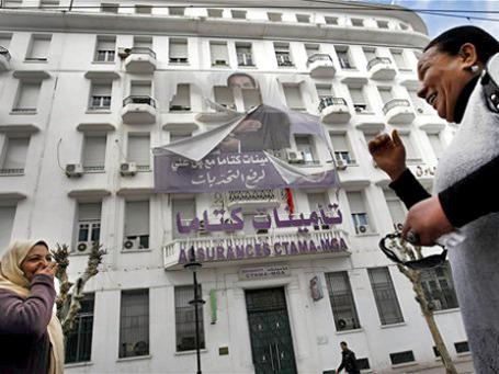 Жительниц столицы Туниса очень забавляет порванное изображение некогда всемогущего президента бен Али, железной рукой правившего страной более 20 лет. Фото: AP