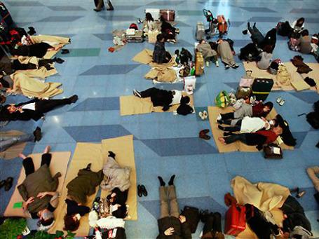 В международном аэропорту Токио ночуют пассажиры отмененных рейсов.  Фото: AP