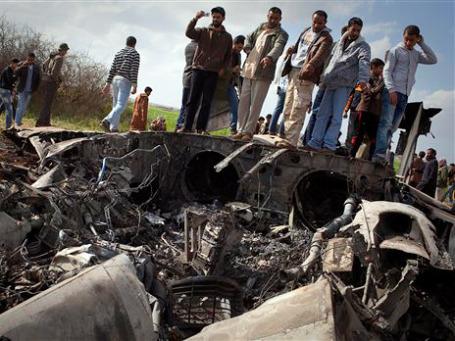 Ливийцы осматривают обломки американского истребителя F15, который разбился в поле около села Bu Mariem, в восточной части Ливии. Фото: AP