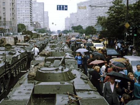 Негероический, но оттого еще более поразительный эпизод августа 1991 года: москвичи под зонтиками проталкиваются между БТР на Калининском проспекте (ныне Новый Арбат). Фото: РИА Новости