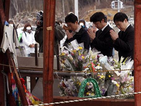 В префектуре Мияги люди молятся, вспоминая жертв 11 марта 2011 года.cФото: AP