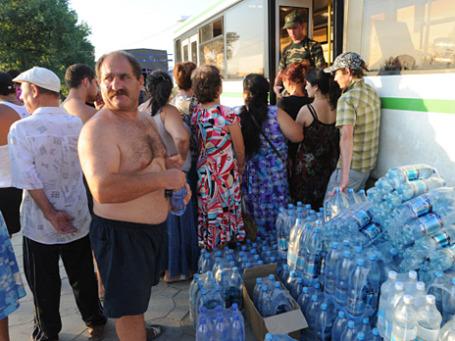 Жители пострадавшего от наводнения города Крымска получают пресную воду в пункте раздачи гуманитарной помощи. Фото: РИА Новости