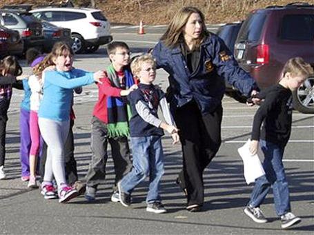 Женщина– полицейский уводит детей начальной школы после сообщения о стрельбе, штат Коннектикут, США. Фото: АР