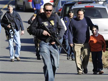 Школьник со своим отцом уходят с места трагедии в школе города Ньютаун, США. Фото: АР