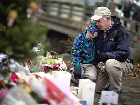 Отец с сыном посещают траурный мемориал в Ньютауне, США. Фото: АР