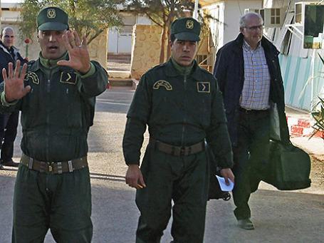 Жандармы сопровождают освобождённого заложника в полицейский участок в городе Ин-Аменас. Фото: Reuters