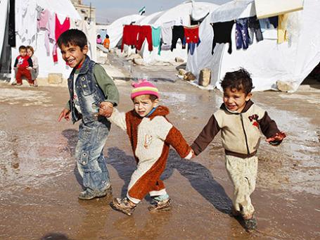 Дети ходят около палаток в лагере для беженцев в Сирии. Фото: Reuters