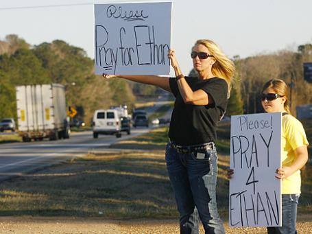 Местные жители штата Алабама вышли на шоссе с плакатами «Молитесь за Итона». Так зовут 5-летнего мальчика, которого держат в заложниках. Фото: Reuters