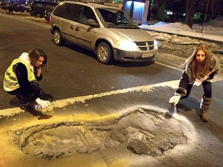 Участники движения «Рассерженные горожане» выделяют краской ямы на дорогах во время акции «Ямы в цвет». Фото: РИА Новости