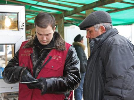 Работник миграционной службы проверяет документы. Фото: fmsmoscow.ru