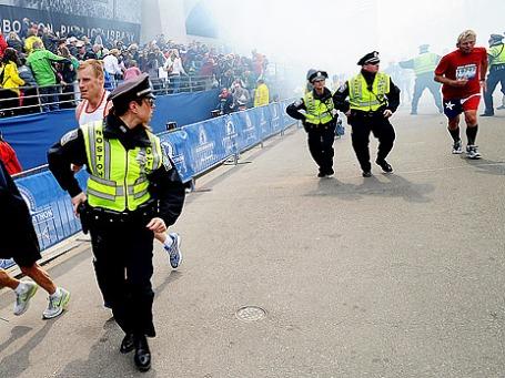 Американские полицейские и спортсмены бегут после двух взрывов на Бостонском марафоне.  Фото: Reuters