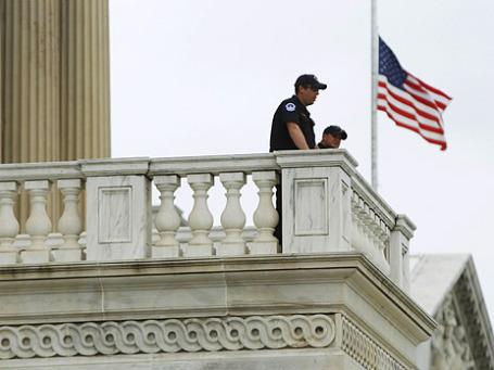 Американские полицейские у приспущенного флага на балконе здания Конгресса США. Фото: Reuters