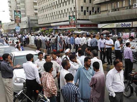 Люди стоят около офисных зданий в Карачи, Пакистан. Землетрясение в иранском городе Хаш, который находится на ирано-пакистанской границе, ощущается и в Пакистане. Фото: Reuters