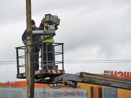 Сотрудник ДПС настраивает камеру автоматической фиксации правил дорожного движения. Фото: РИА Новости