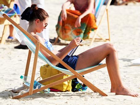 Девушка читает книгу на пляже в парке Горького в Москве. Фото: РИА Новости