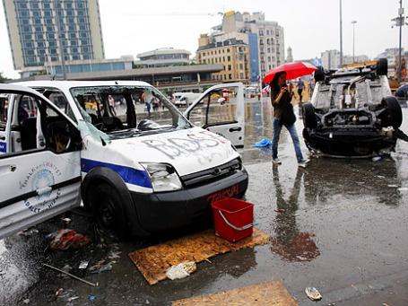 Женщина проходит мимо повреждённой полицейской машины на площади Таксим, где прошли столкновения антиправительственных демонстрантов с полицией. Фото: Reuters