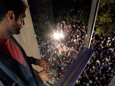 Сотрудник главной гостелерадиокомпании Греции ERT смотрит из окна здания на людей, пришедших выразить протест против решения правительства о закрытии ERT. Фото: Reuters
