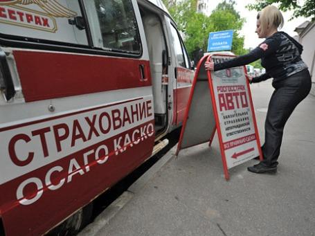 Сотрудница передвижного пункта страхования автомобилей выставляет рекламный штендер перед началом рабочего дня. Фото: РИА Новости