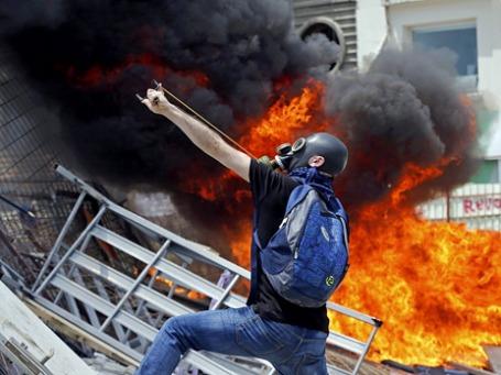 Участник антиправительственных демонстраций во время столкновений с полицией в Стамбуле. Фото: Reuters