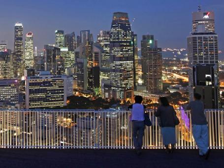 Люди любуются ночным видом центра Сингапура. Фото: Reuters
