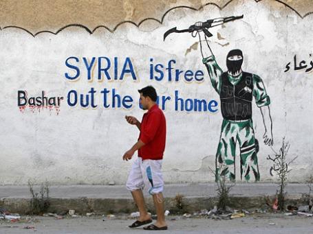 Прохожий идет мимо забора с надписью  «Свободная Сирия, Башар уходи из нашего дома». Фото: Reuters