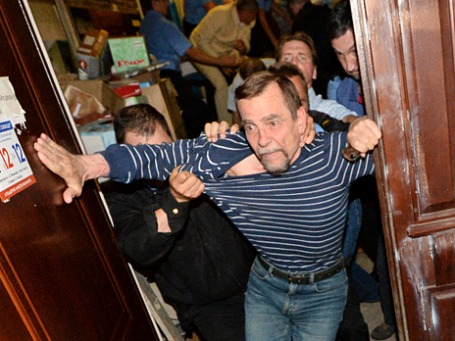 Сотрудники охранного предприятия выгоняют исполнительного директора движения «За права человека»  Льва Пономарева из здания правозащитной организации в Малом Кисловском переулке. Фото: РИА Новости