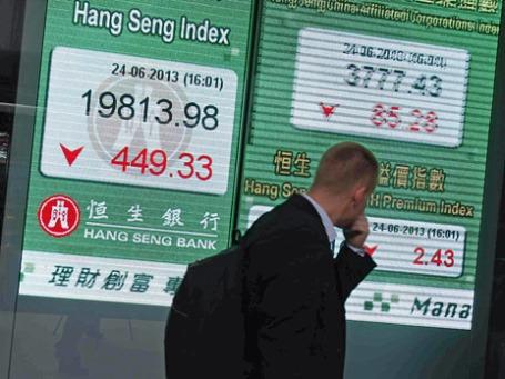 Мужчина проходит мимо экрана, показывающего значения биржевых индексов. Фото: Reuters