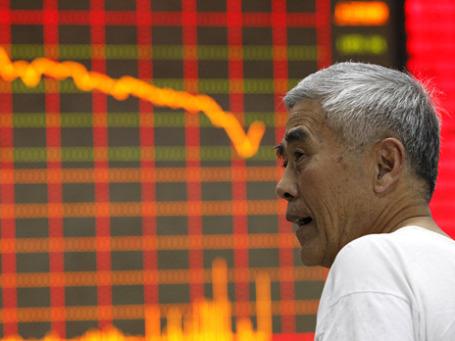 Работник брокерской конторы напротив экрана с показателями фондового индекса. Фото: Reuters