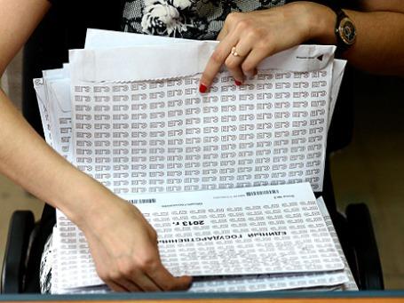 Сотрудница Института мониторинга и развития образования принимает бланки, доставленные из пунктов проведения ЕГЭ для обработки результатов. Фото: РИА Новости