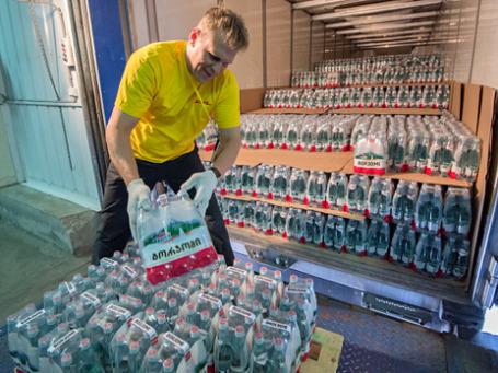Сотрудник складских служб выгружает партию воды «Боржоми». Фото: РИА Новости
