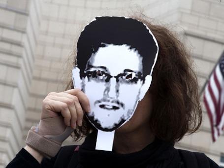 Женщина держит маску с изображением Эдварда Сноудена. Фото: Reuters