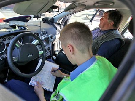 Офицер дорожно-патрульной службы ГИБДД оформляет протокол о нарушении правил дорожного движения. Фото: РИА Новости