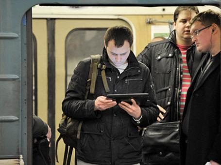 Пассажир с планшетным компьютером в вагоне поезда. Фото: РИА Новости