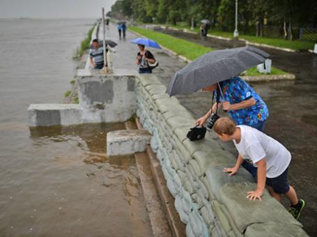 Жители Хабаровска на набережной реки Амур у противопаводковых заграждений из мешков с песком.  Фото: РИА Новости