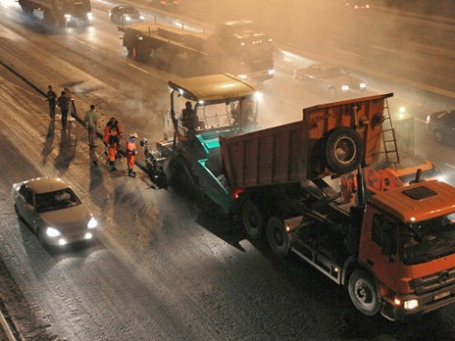 Сотрудники дорожно-ремонтной службы во время укладки асфальтового покрытия на Московской кольцевой автомобильной дороге. Фото: РИА Новости