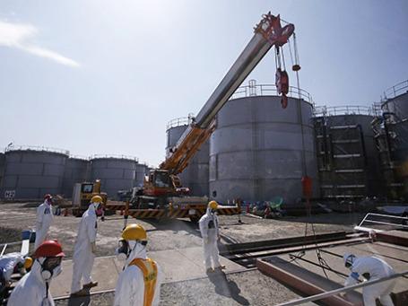 Сотрудники Tokyo Electric Power в защитных костюмах рядом с резервуарами загрязненной воды. Фото: Reuters
