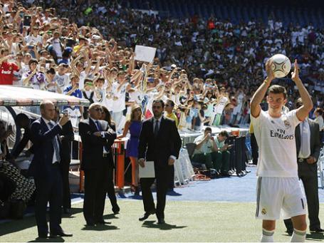 Футболист Гаррет Бэйл (справа) приветствует болельщиков после официального объявления его игроком команды «Реал Мадрид» на стадионе Сантьяго Бернабеу в Мадриде. Фото: Reuters