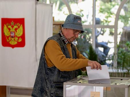 Мужчина опускает избирательный бюллетень в урну для голосования на избирательном участке. Фото: РИА Новости