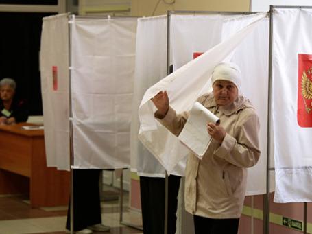 Женщина выходит из кабины во время голосования. Фото: РИА Новости