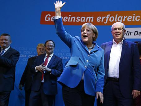 Канцлер Германии и лидер Христианско-демократического союза (ХДС) Ангела Меркель приветствует сторонников вместе с лидером парламентской фракции ХДС Фолькером Каудером (справа) в штаб-квартире партии в Берлине после первых данных экзит-поллов 22 сентября 2013 года. Меркель одержала уверенную победу на выборах, и впервые за полвека в Германии партия власти может рассчитывать на абсолютное большинство в парламенте. Фото: Reuters