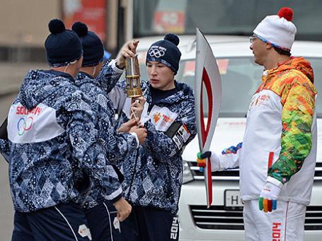 Хранители огня поджигают факел от лампадки во время эстафеты Олимпийского огня в Москве. Фото: РИА Новости