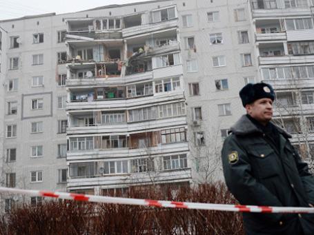 Сотрудник правоохранительных органов перед девятиэтажным домом в поселке Загорские Дали на севере Московской области, в котором произошел взрыв бытового газа. Фото: РИА Новости